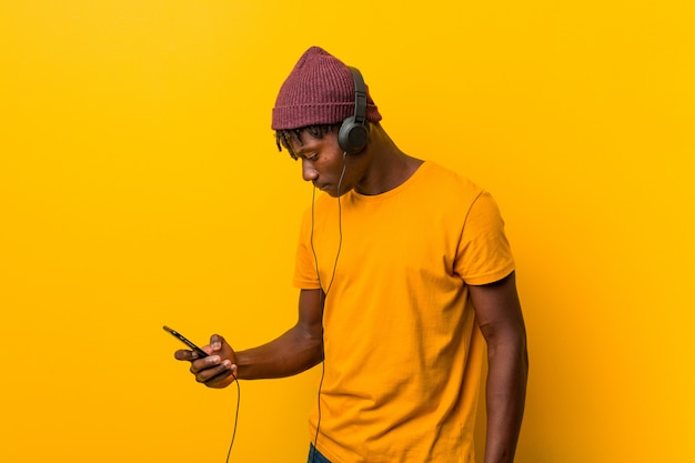 携帯電話で音楽を聞いて帽子をかぶって黄色に対して立っている若いアフリカ人 Premium写真