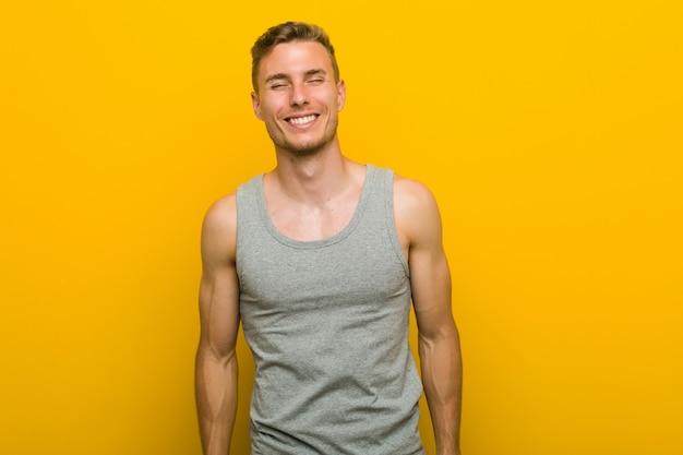 若い白人スポーツ男は笑って目を閉じて、リラックスして幸せを感じています。 Premium写真