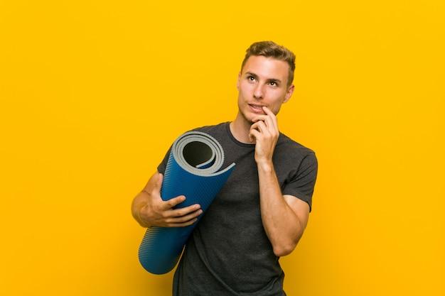 マットを保持している若い白人男は、コピースペースを見て何かを考えてリラックスしました。 Premium写真