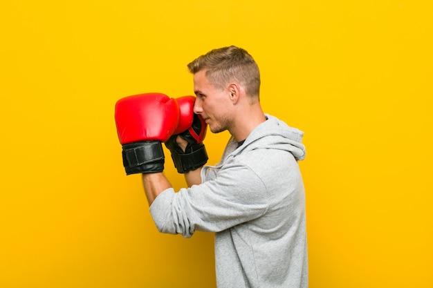 ボクシンググローブを身に着けている若い白人男 Premium写真