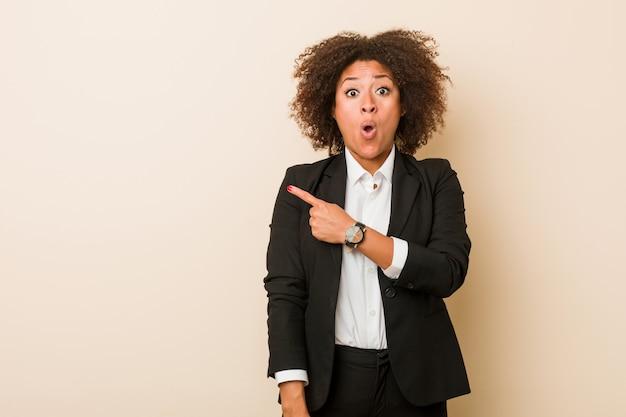 側を指している若いビジネスアフリカ系アメリカ人女性 Premium写真