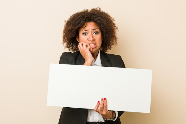 Молодая афро-американская женщина держа ногти плаката сдерживая, слабонервный и очень тревоженый. Premium Фотографии
