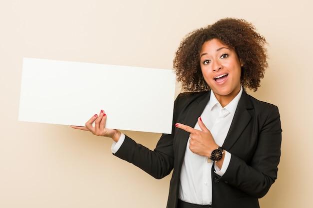 Молодая афро-американская женщина проводя плакат усмехаясь жизнерадостно указывая с указательным пальцем прочь. Premium Фотографии