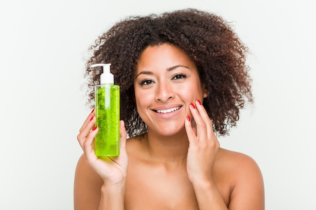 Закройте вверх молодой красивой и естественной афро-американской женщины держа бутылку алоэ вера Premium Фотографии