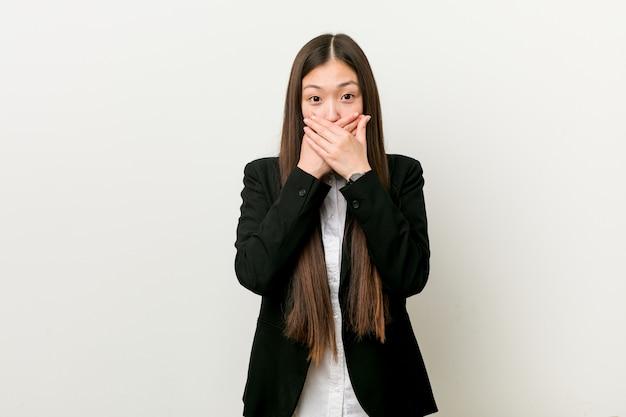 若いかなり中国のビジネス女性は手で口を覆ってショックを受けた。 Premium写真
