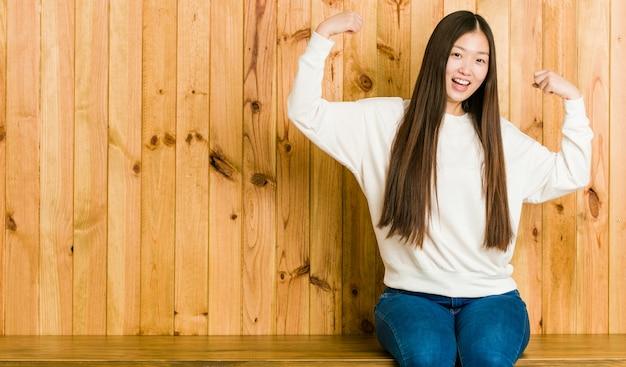 腕、女性の力の象徴と強度ジェスチャーを示す木製の場所に座っている若い中国人女性 Premium写真