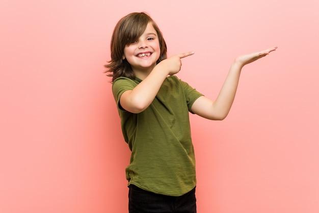 Маленький мальчик взволнован, держа копией пространства на ладони. Premium Фотографии