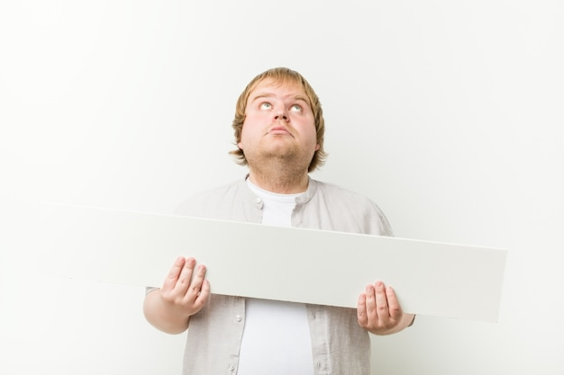 プラカードを持つ白人クレイジーブロンドデブ男 Premium写真