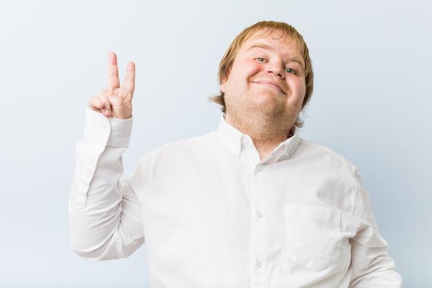 指で平和のシンボルを示すうれしそうな屈託のない若い本物の赤毛デブ男。 Premium写真