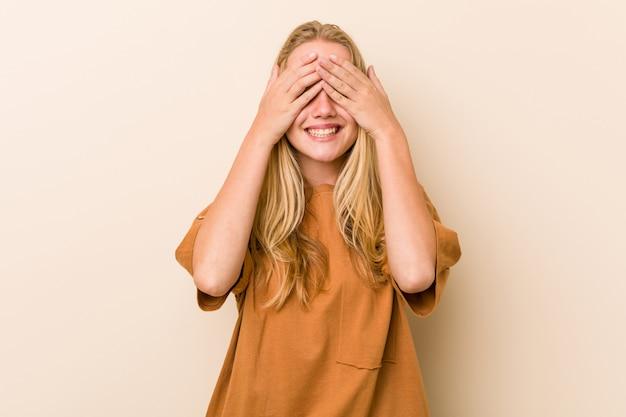 キュートで自然なティーンエイジャーの女性は、目を手で覆い、笑顔は広く驚きを待っています。 Premium写真