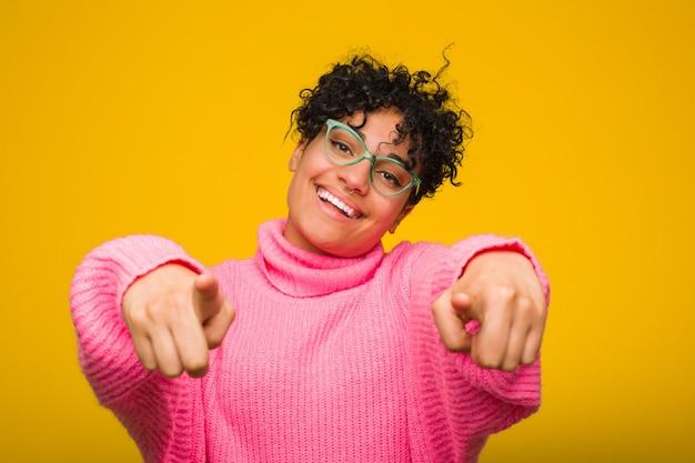 前面を指しているピンクのセーター陽気な笑顔を着ている若いアフリカ系アメリカ人女性。 Premium写真