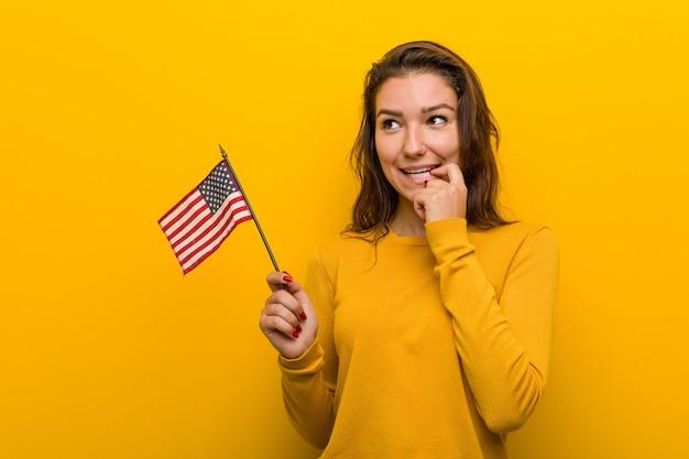 Молодая женщина держа флаг соединенных штатов ослабила думать о что-то смотря экземпляр. Premium Фотографии