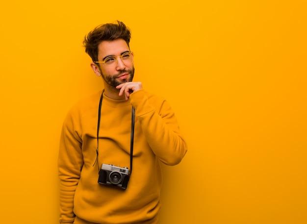 疑って混乱している若い写真家の男 Premium写真