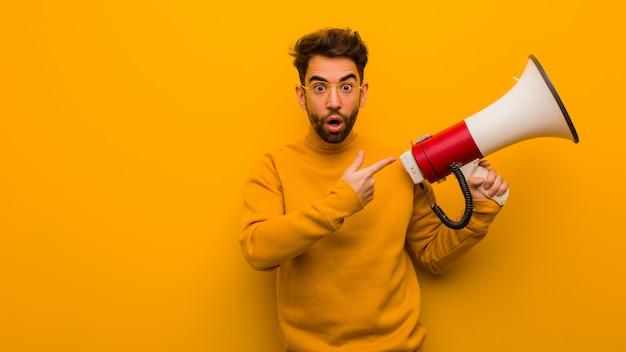 Молодой человек держит мегафон, что-то держит рукой Premium Фотографии