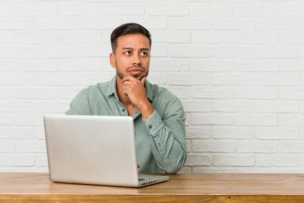 疑わしいと懐疑的な表情で横に見て彼のラップトップで働いて座っている若いフィリピン人。 Premium写真