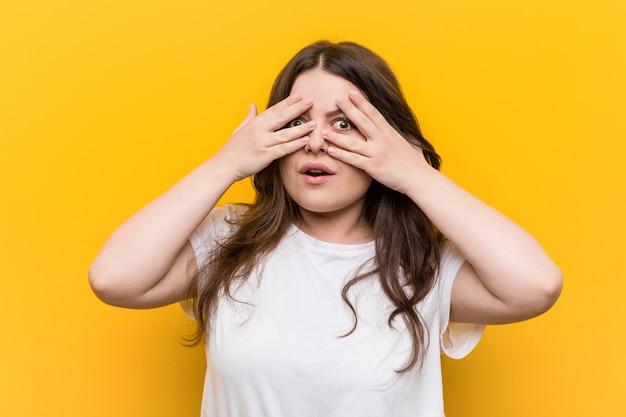 Молодая соблазнительная женщина плюс размер моргает сквозь пальцы испуганно и нервно. Premium Фотографии