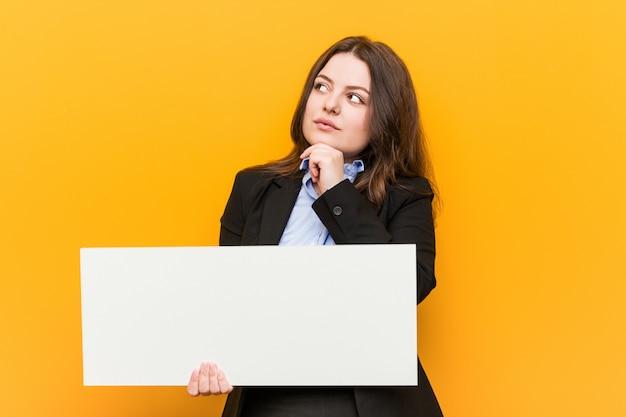 疑いと懐疑的な表情で横向きのプラカードを保持している若いプラスのサイズの曲線の女性。 Premium写真
