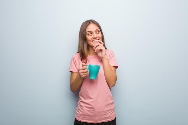 かなり白人の若い女性は、コピーを見て何かについて考えてリラックスしました。彼女はマグカップを持っています。 Premium写真