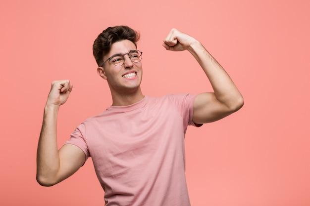 勝利、勝者の後拳を上げる若いクールな白人男性。 Premium写真