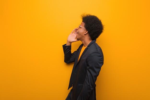 Молодой человек афроамериканца дела над оранжевой стеной шепча сплетне подтекст Premium Фотографии
