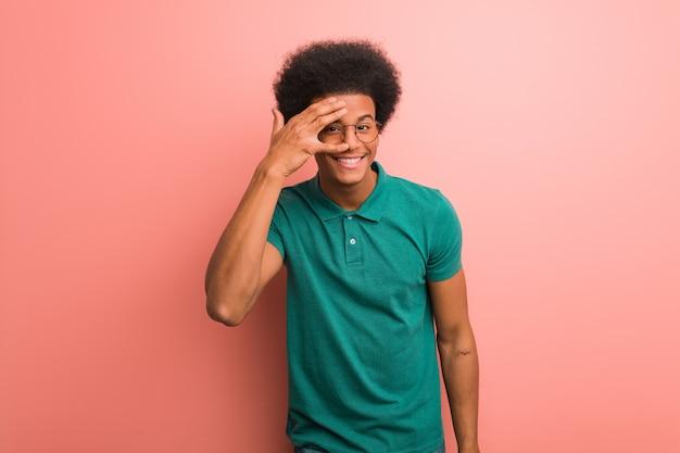 ピンクの壁の上の若いアフリカ系アメリカ人の男が恥ずかしいと笑いながら Premium写真
