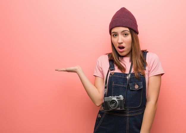 Молодая милая женщина фотографа что-то держит на ладони Premium Фотографии