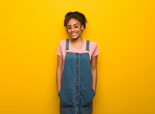 笑顔で陽気な青い目を持つ若い黒人アフリカ系アメリカ人の女の子 Premium写真