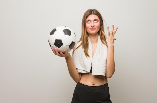 ロシアの若いフィットネス女性は非常に恐れています。サッカーボールを保持しています。 Premium写真
