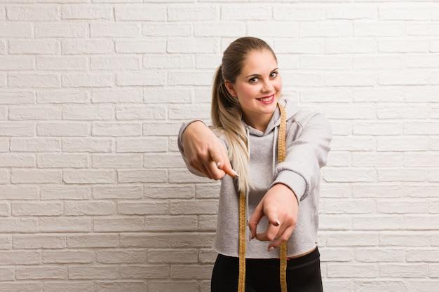 メジャーテープを保持している若いフィットネスロシア女性 Premium写真