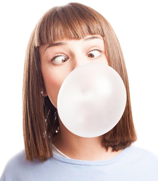 チューインガムでバブルをやっているおかしい女の子 無料写真