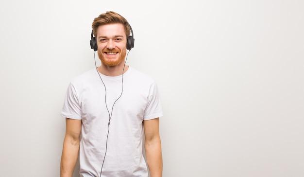 大きな赤毛の陽気な若い赤毛の男。ヘッドフォンで音楽を聴く。 Premium写真