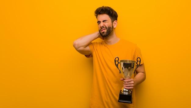 首の痛みに苦しんでいるトロフィーを保持している若い男 Premium写真