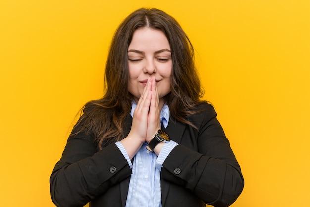口の近くで祈って手を繋いでいる若いプラスのサイズの白人女性は自信を持って感じています。 Premium写真