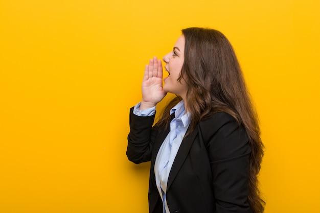 若いプラスサイズの白人女性が叫び、開いた口の近くの手のひらを保持しています。 Premium写真