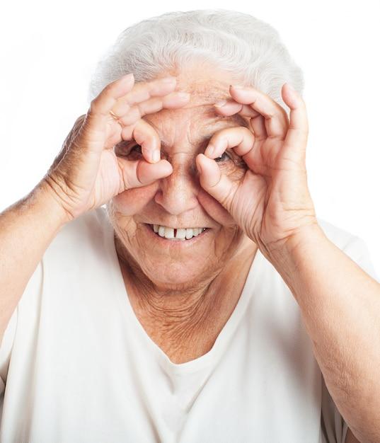 Пожилая женщина делает очки с ее пальцами Бесплатные Фотографии