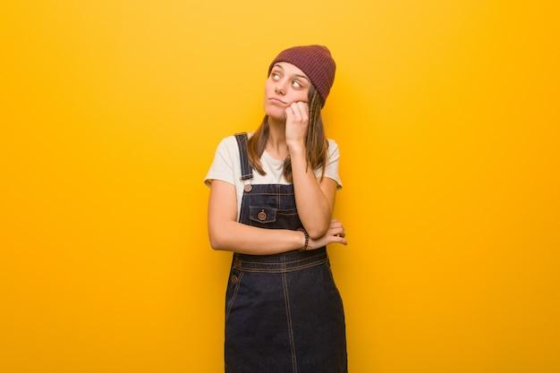 何かを考えて、側にいる若い流行に敏感な女性 Premium写真