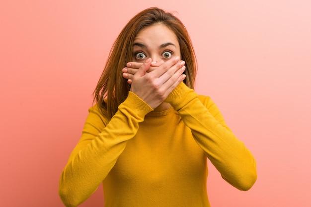 若いかなり若い女性は手で口を覆ってショックを受けた。 Premium写真