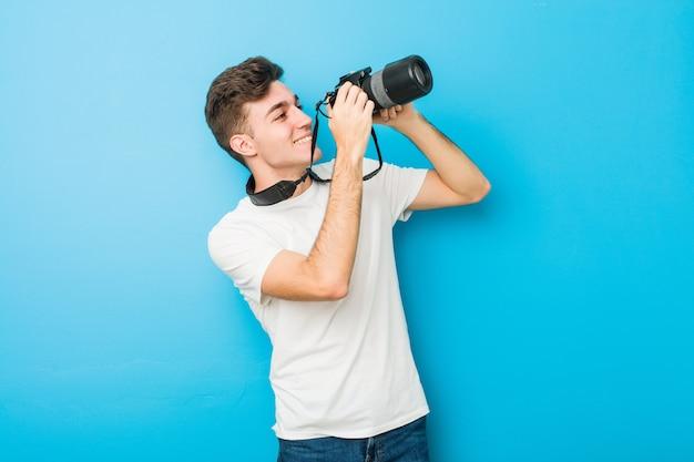反射カメラで写真を撮るティーンエイジャーの白人男性 Premium写真
