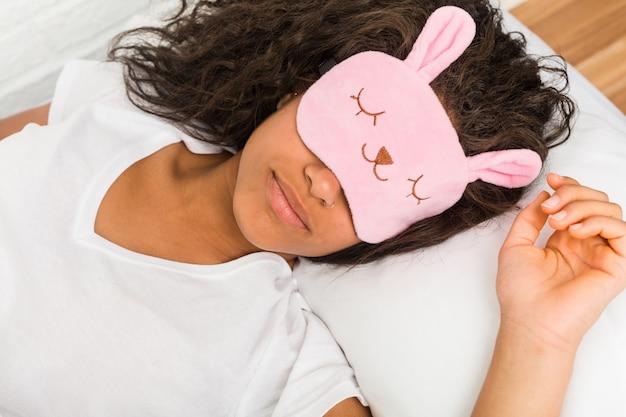 Крупным планом молодой афроамериканец устал женщина спит на кровати Premium Фотографии