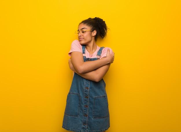抱擁を与える青い目を持つ若い黒アフリカ系アメリカ人少女 Premium写真