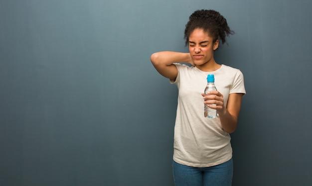 Молодая негритянка страдает боль в шее. она держит бутылку с водой. Premium Фотографии