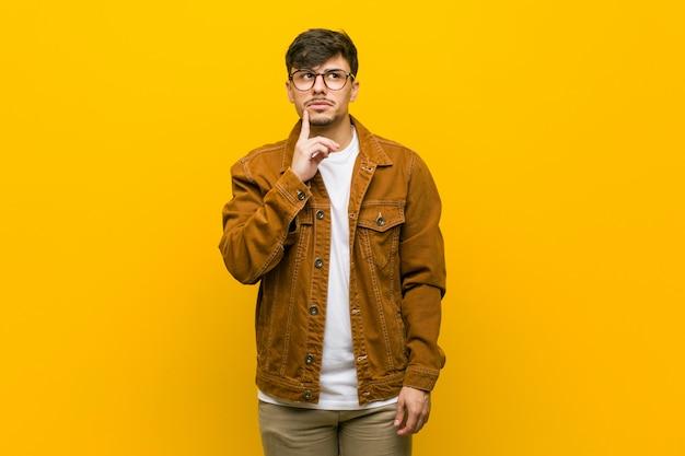 疑わしいと懐疑的な表情で横に見ている若いヒスパニックのカジュアルな男。 Premium写真