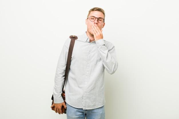 Молодой кавказский бизнесмен зевая показывая утомленный жест покрывая рот рукой. Premium Фотографии