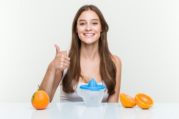 笑みを浮かべて、親指を上げるオレンジジューサーを持つ若い白人女性 Premium写真