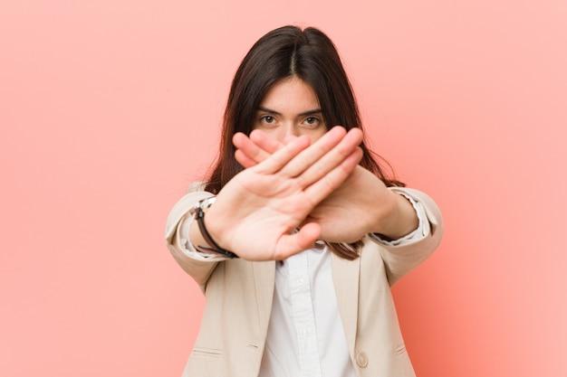 Молодая брюнетка деловая женщина против розового делает жест отрицания Premium Фотографии