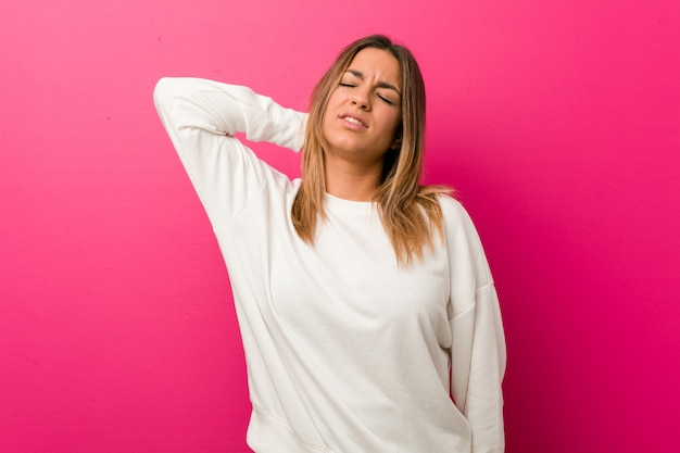 座りがちな生活のために首の痛みに苦しんでいる壁に対して若い本物のカリスマ的な実在の女性。 Premium写真