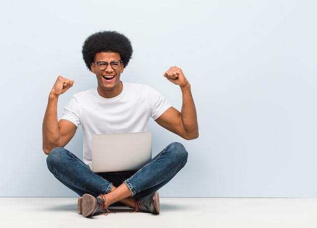 降伏しないラップトップで床に座っている若い黒人男性 Premium写真