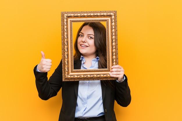 若い実業家笑顔と親指を上げるフレームを保持 Premium写真