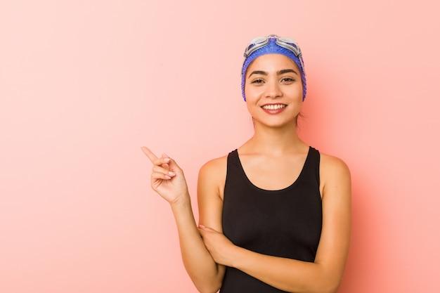 人差し指で元気に指している笑顔若いスイマー女性 Premium写真