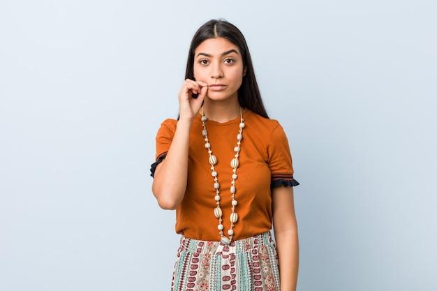 秘密を保つ唇に指を持つ若い女性 Premium写真